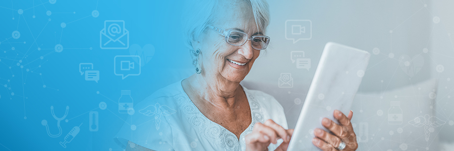Elderly woman smiling while using a tablet.