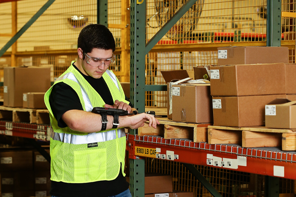 A male warehouse worker using a handheld device that is managed and secured by SOTI's MDM solution