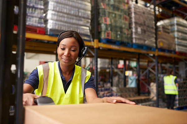 A female warehouse worker using a scanner that is managed and secured by SOTI's MDM solution
